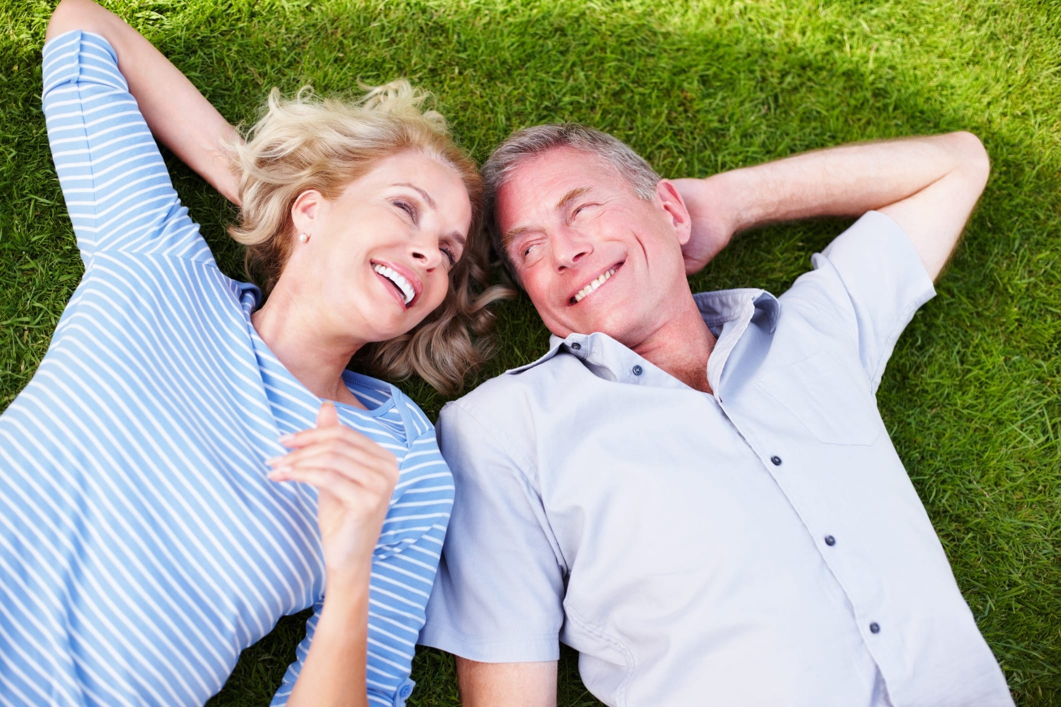 high net worth wealthy retired couple lying on green grass